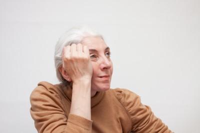 頭を抱えるシニア女性